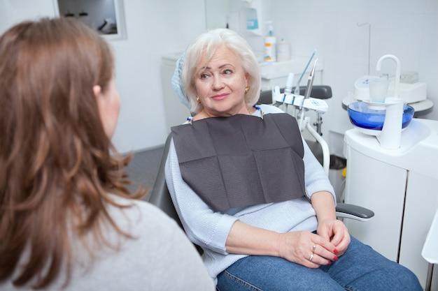 Прекрасная старшая женщина разговаривает со своим стоматологом после стоматологического осмотра