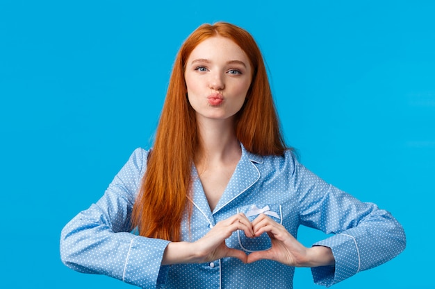 Lovely sensual good-looking redhead female with long ginger hair, freckles, folding lips for kiss