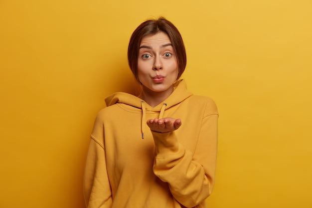 素敵な官能的な女性は、距離に別れを告げ、手のひらを前に保ち、丸い唇を持ち、エアキスを送り、mwahを吹き、健康な肌を持ち、スウェットシャツを着て、黄色い壁にポーズをとります。ロマンス、優しさ