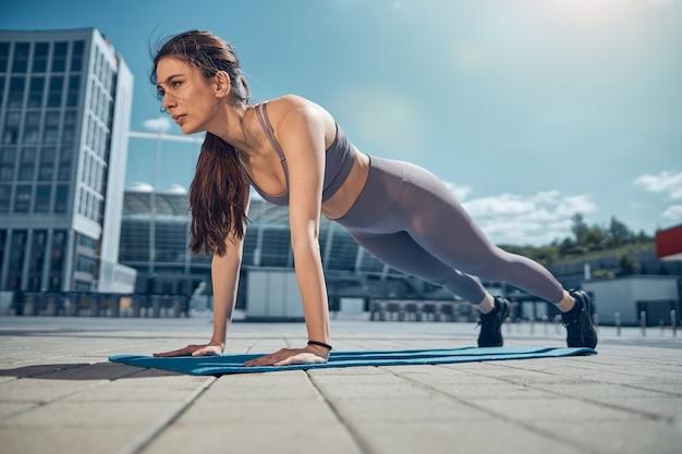 マットの上で高い板の運動を行う素敵な真面目な運動黒髪の若い白人女性