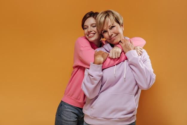 Прекрасная девушка с короткими волосами в модной толстовке с капюшоном и джинсах улыбается с закрытыми глазами и обнимает свою мать в стильной одежде на оранжевом фоне.