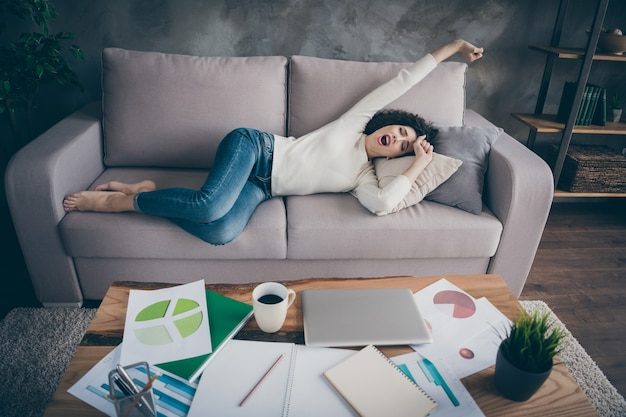 Lovely sleepy peaceful   girl lying on sofa having rest waking up stretching yawning in modern loft industrial style interior living-room indoors