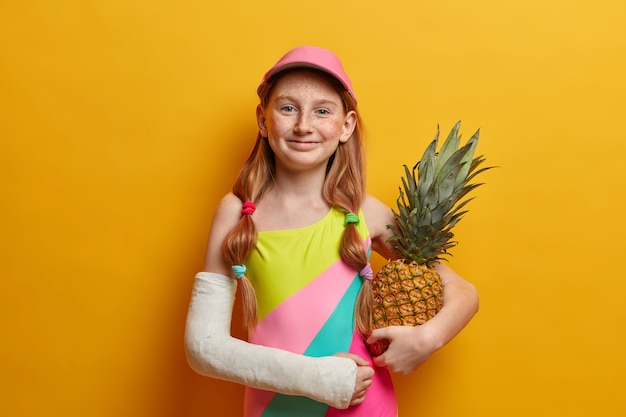Adorabile bambina in costume da bagno colorato e berretto, posa con ananas contro il muro giallo, gode dell'estate e del buon riposo, ha un braccio rotto dopo una caduta dall'altezza o uno sport pericoloso