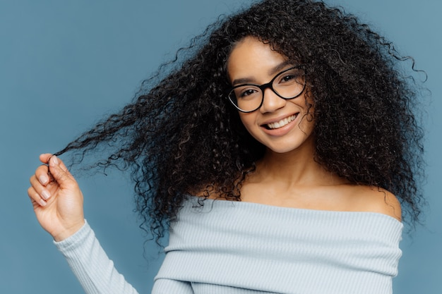 Lovely smiling afro american woman holds tips of her curly hair, wears fashionable light blue sweater