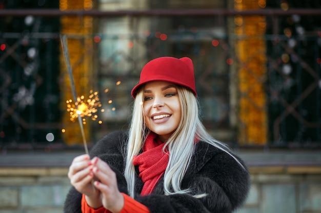 花輪のボケ味の背景で新年を祝うトレンディな赤い帽子をかぶって素敵な笑顔のブロンドの女性