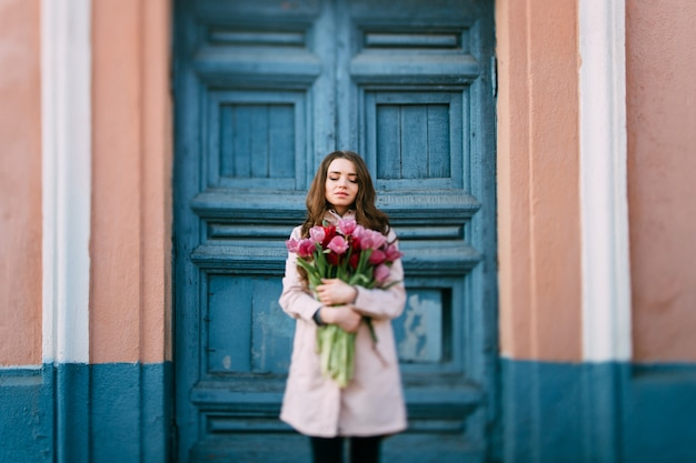 Lovely smiling brunette woman standing in front of old  door with a bouquet of fresh tulips.