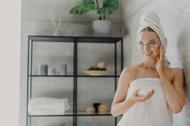 Lovely smiling caucasian woman applies beauty cream on cheek, enjoys morning domestic skin care routine, wrapped in bath towel, grooming herself after showering poses in bathroom. hygiene concept