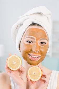 Lovely, smiling girl in white towel and brown mud facial mask having fun with two halves of lemon, indoor shot in the white space
