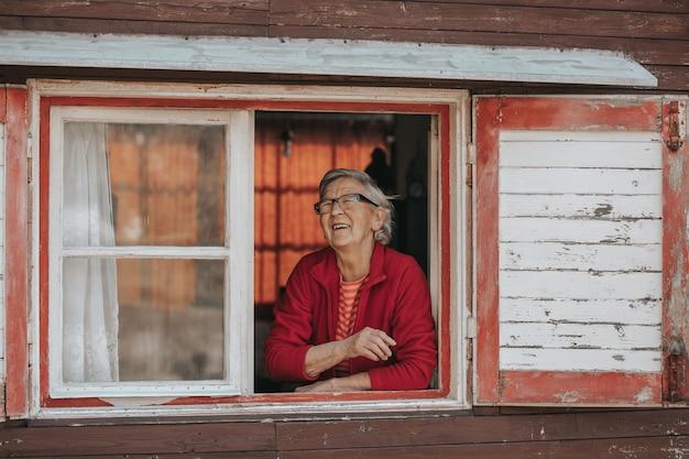 Милая улыбающаяся бабушка смотрит в окно и наслаждается солнечным днем, пенсионной жизнью.