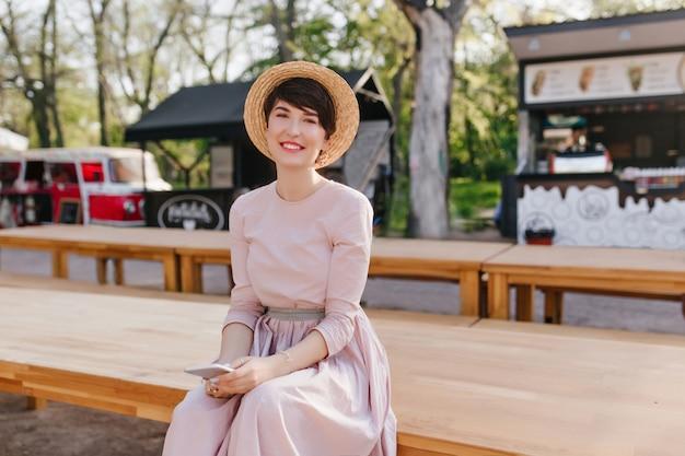 膝の上に横たわっている手でテーブルに座っているロマンチックな服装で素敵な笑顔の女性