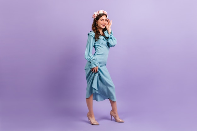 Lovely smiling lady in satin blue outfit. woman touches her face on lilac wall.