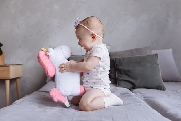 Lovely smiling little girl with a hoop is playing with toy unicorn on bed at home. concept of childhood day.