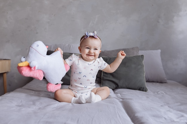 Lovely smiling little girl with a hoop is playing with toy unicorn on bed at home.