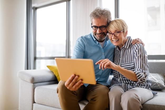 집에서 태블릿을 사용하면서 즐겁게 웃고 있는 사랑스러운 성숙한 부부