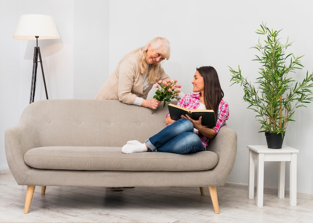 Lovely smiling senior mother giving flower bouquet to her daughter sitting on sofa holding book in hand