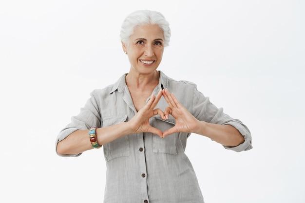 Прекрасная улыбающаяся старшая женщина, показывающая жест сердца