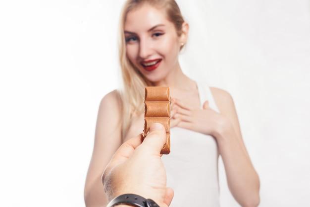 チョコレートを食べる素敵な笑顔の 10 代の少女