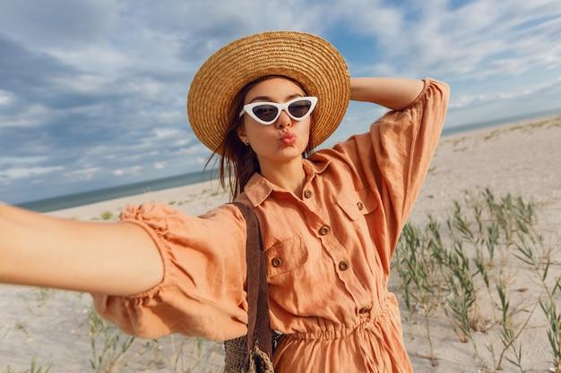 Прекрасная улыбающаяся женщина, делающая автопортрет и наслаждающаяся отдыхом на берегу океана. в модных солнцезащитных очках в стиле ретро и соломенной шляпе.
