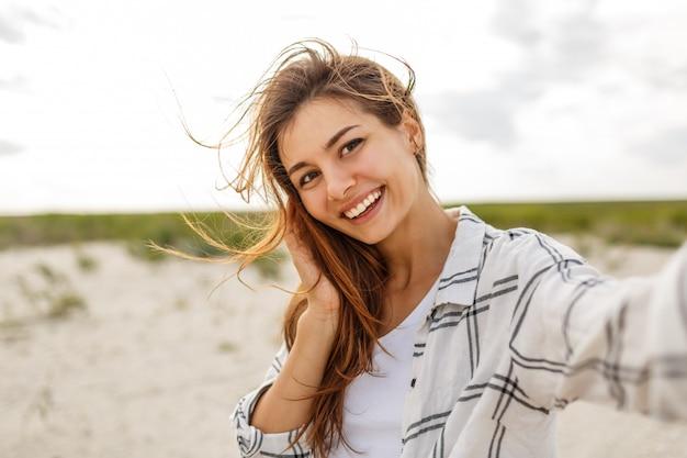 Прекрасная улыбающаяся женщина, делающая автопортрет и наслаждающаяся отдыхом на берегу океана.
