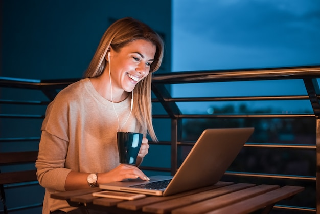 Lovely smiling woman using laptop at night.