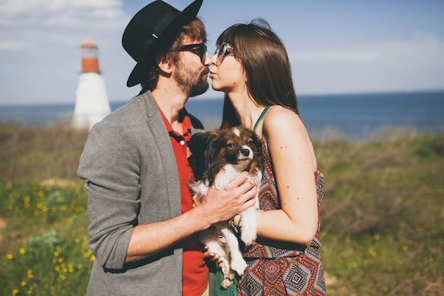 Милые улыбающиеся молодые стильные хипстерские влюбленные пары гуляют с собакой в сельской местности