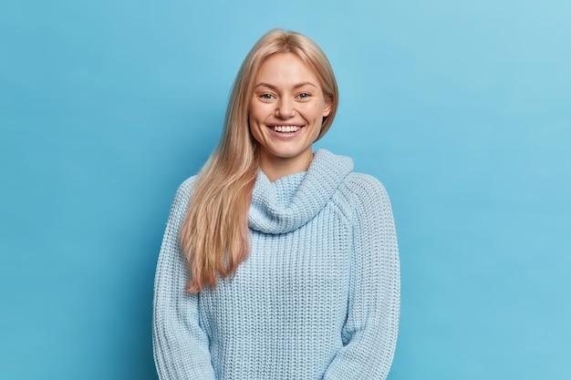 Милая улыбающаяся молодая женщина со светлыми волосами выражает положительные эмоции, имеет идеальные белые зубы, одетая в вязаный теплый джемпер