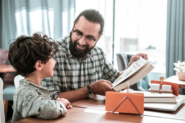 Lovely son. happy dad wearing squared shirt looking at his lovely cute son reading book together