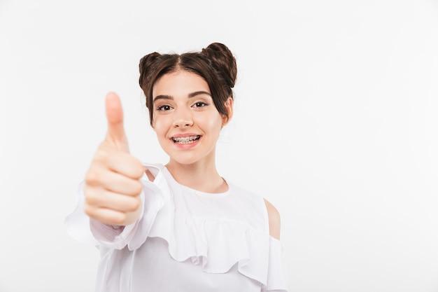 Милая студентка с двойной прической и брекетами улыбается, показывая большой палец вверх, изолирована на белом