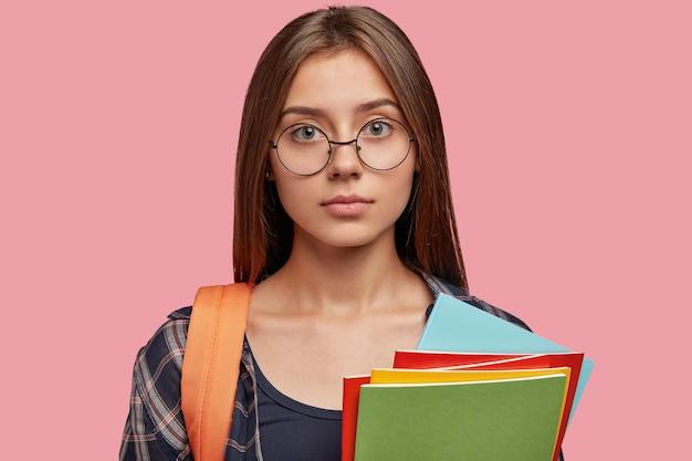 Bella studentessa in posa contro il muro rosa con gli occhiali