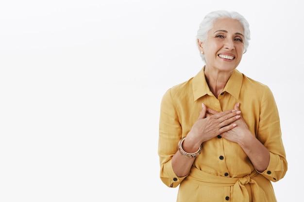 사랑스러운 세련된 노인 여성이 마음에 손을 잡고 기쁘게 웃고