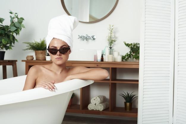 素敵なスタイリッシュな女の子がお風呂に入ります。スパサロンの女性。ホテルでサングラスをかけた女の子