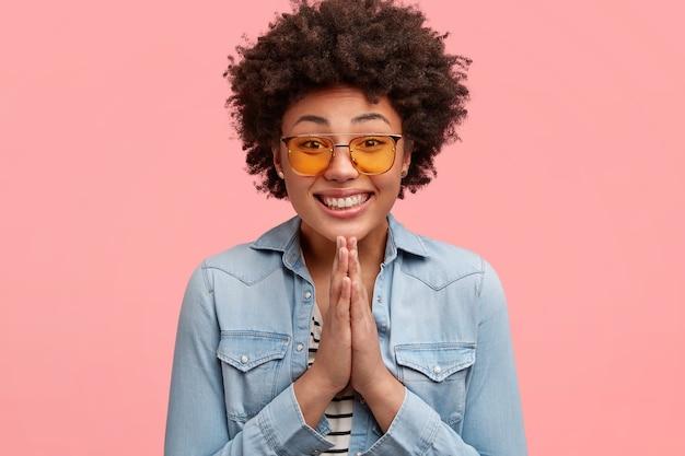Bella ed elegante giovane donna afroamericana con un ampio sorriso e un'espressione supplichevole, tiene le mani nel gesto di preghiera, chiede qualcosa, indossa una giacca di jeans e occhiali da sole gialli alla moda