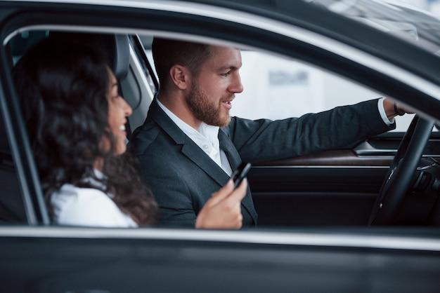 Прекрасная успешная пара пробует новую машину в автомобильном салоне.