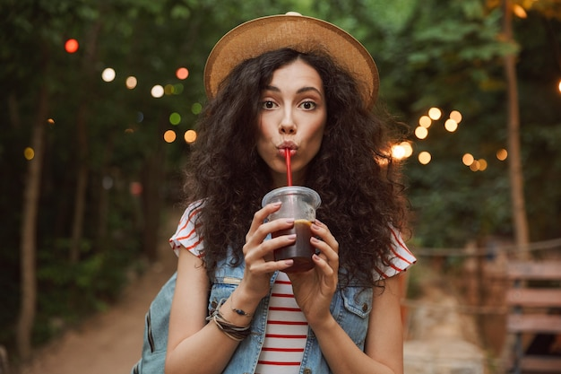 Lovely summer woman wearing straw hat, looking at you while drinking beverage from plastic cup during rest in green park with colorful lamps