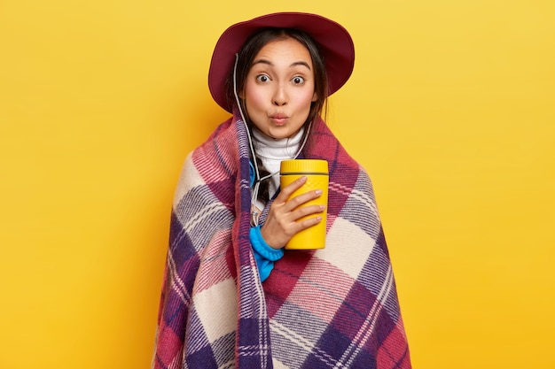 Lovely surprised female traveler has active camping rest, warms with hot beverage and checkered plaid, keeps lips folded