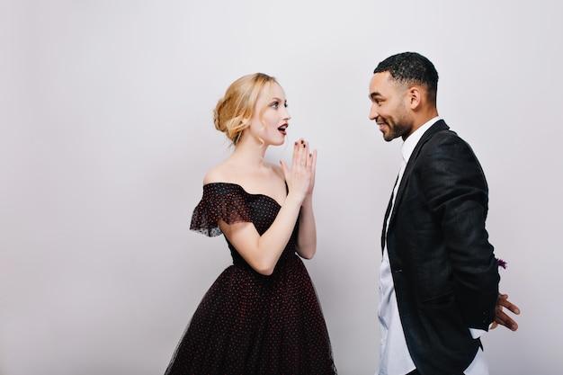 Прекрасные наряды привлекательной изумленной молодой женщины в роскошном вечернем платье и красивого мужчины в смокинге на свиданиях.