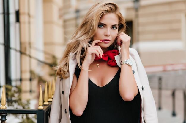 素敵な日焼けした女性モデルは、日付の前にポーズをとって金色の宝石を着ています。