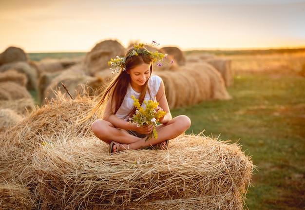 Милая девушка с цветочным букетом на стоге сена