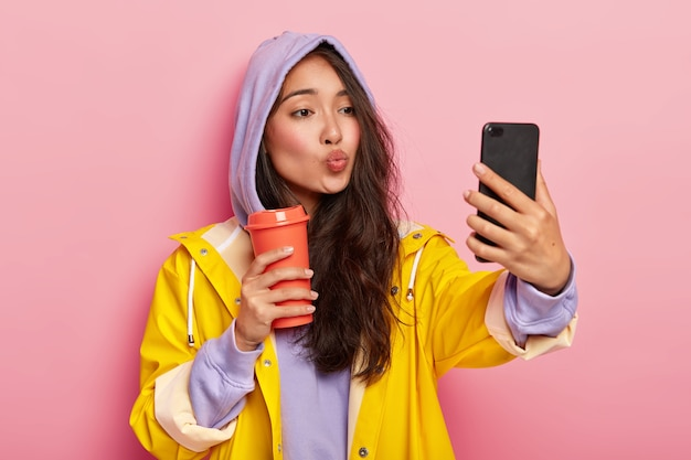 Lovely teenage girl with asian appearance, keeps lips folded, sends kiss at camera of cellphone, takes selfie, enjoys drink, wears sweatshirt, hood on head, yellow raincoat, has walk after rain