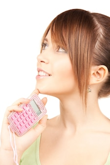 Lovely teenage girl with calculator over white