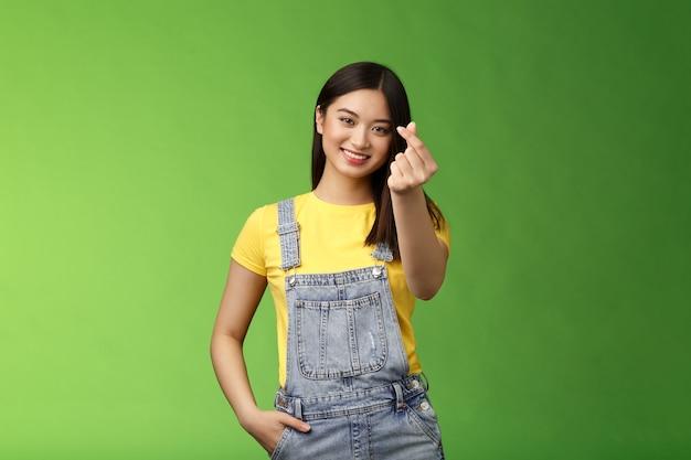 素敵な優しいのんきなアジアのガールフレンドショー韓国の愛のサインは指の心をかわいい笑顔にします