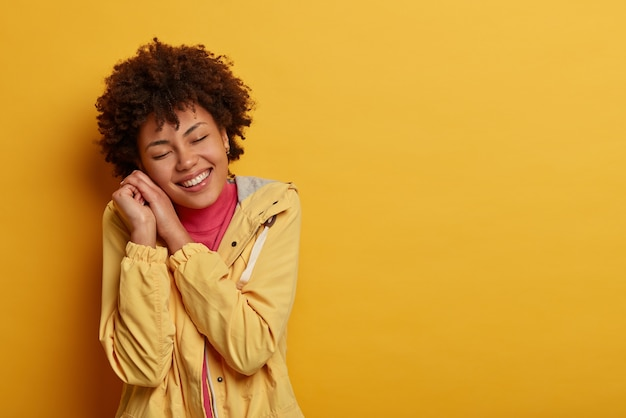 素敵な優しい女性は目を閉じて両手に頭をもたせ、楽しい夢を見て、心から笑顔で、白い歯を見せます