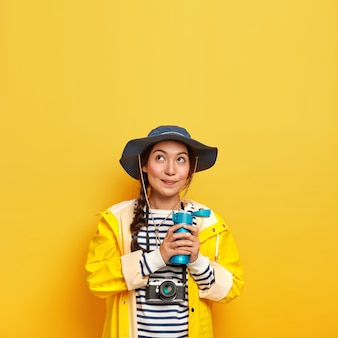 Lovely thoughtful girl in stylish headgear, protective raincoat, holds thermos with hot drink, carries retro camera for making photographes, creats content
