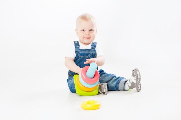 白い背景で隔離のカメラに笑みを浮かべて座って遊んでいるデニムスーツの素敵な幼児。
