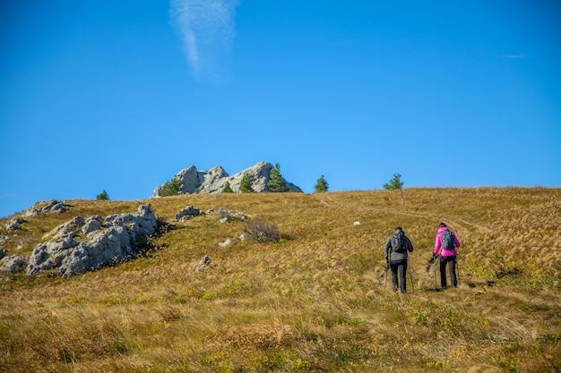 青い空の下でスロベニアのロッキー山脈を登る素敵な観光客のカップル