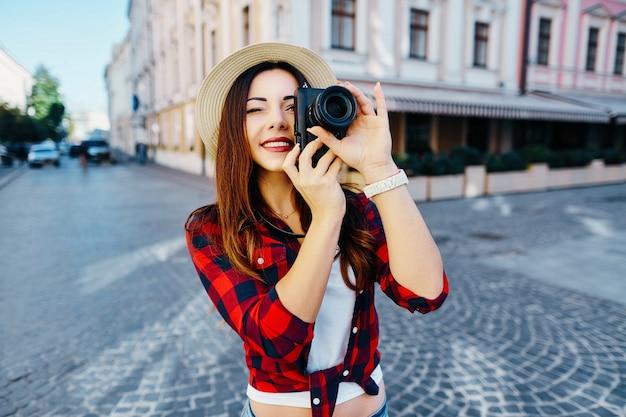 Прекрасная туристическая девушка с каштановыми волосами в шляпе и красной рубашке, делая фото с камерой на фоне старого европейского города и улыбаясь, путешествуя.