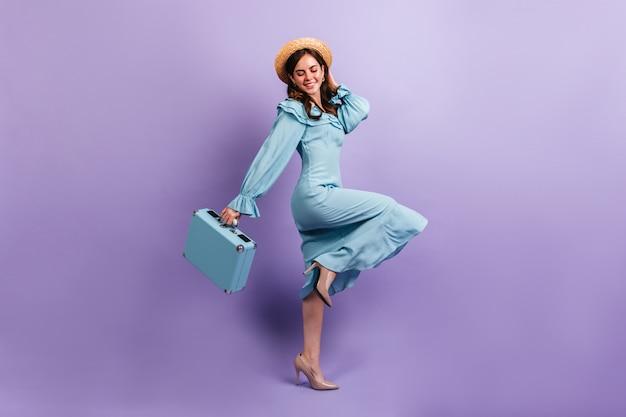 실크로 만든 미디 드레스를 입은 사랑스러운 여행자가 보라색 벽에 행복하게 포즈를 취합니다. 가방 밀 짚 모자에있는 여자의 전체 길이 샷.