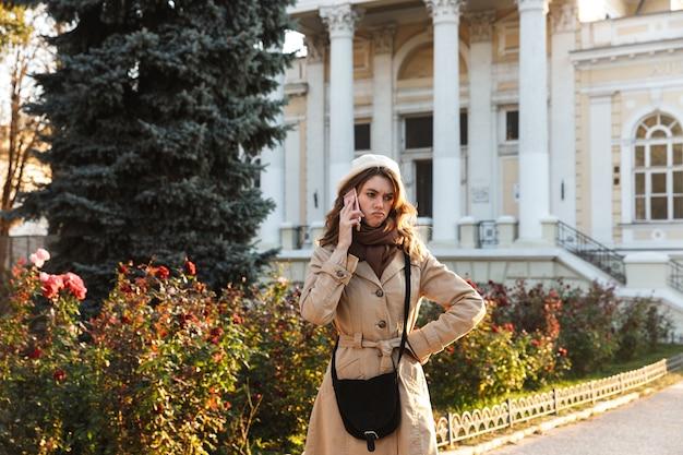 屋外を歩いて、携帯電話で話しているコートを着て素敵な動揺の若い女性