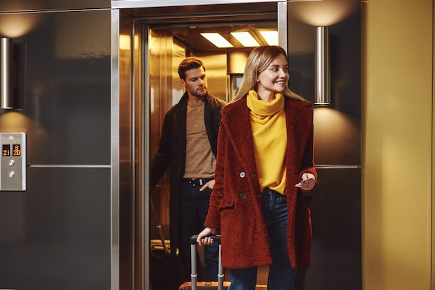 멋진 휴가. 사랑스러운 커플은 낭만적인 휴가에 호텔 층으로 들어갑니다. 그들은 호텔 엘리베이터에서 온다