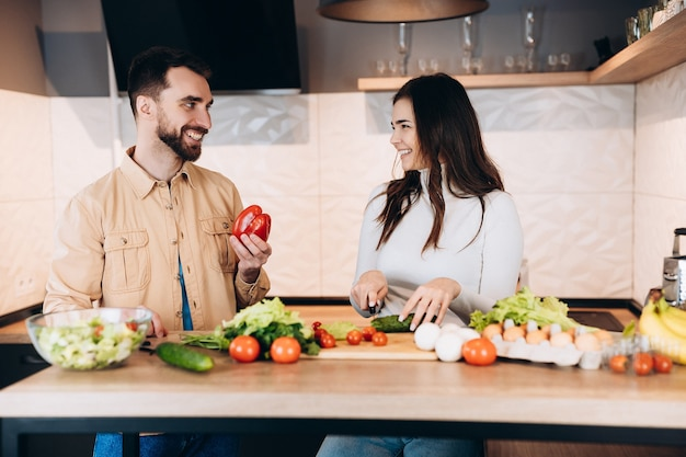 Lovely vegetarian couple is cooking together in the kitchen and using only fresh and nutrition products because they live healthy lifestyle.
